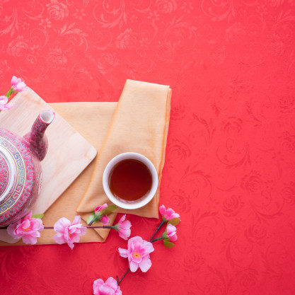 teapot-cup-tea-cherry-blossom-red-tablecloth-background_45281-254